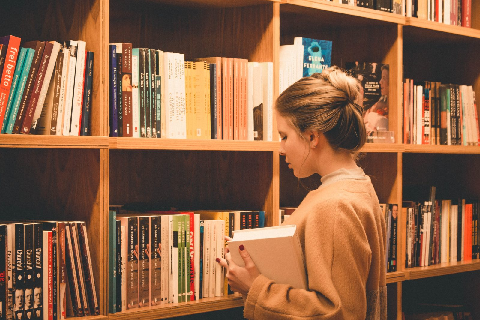 Girl Student in Library looking at Books