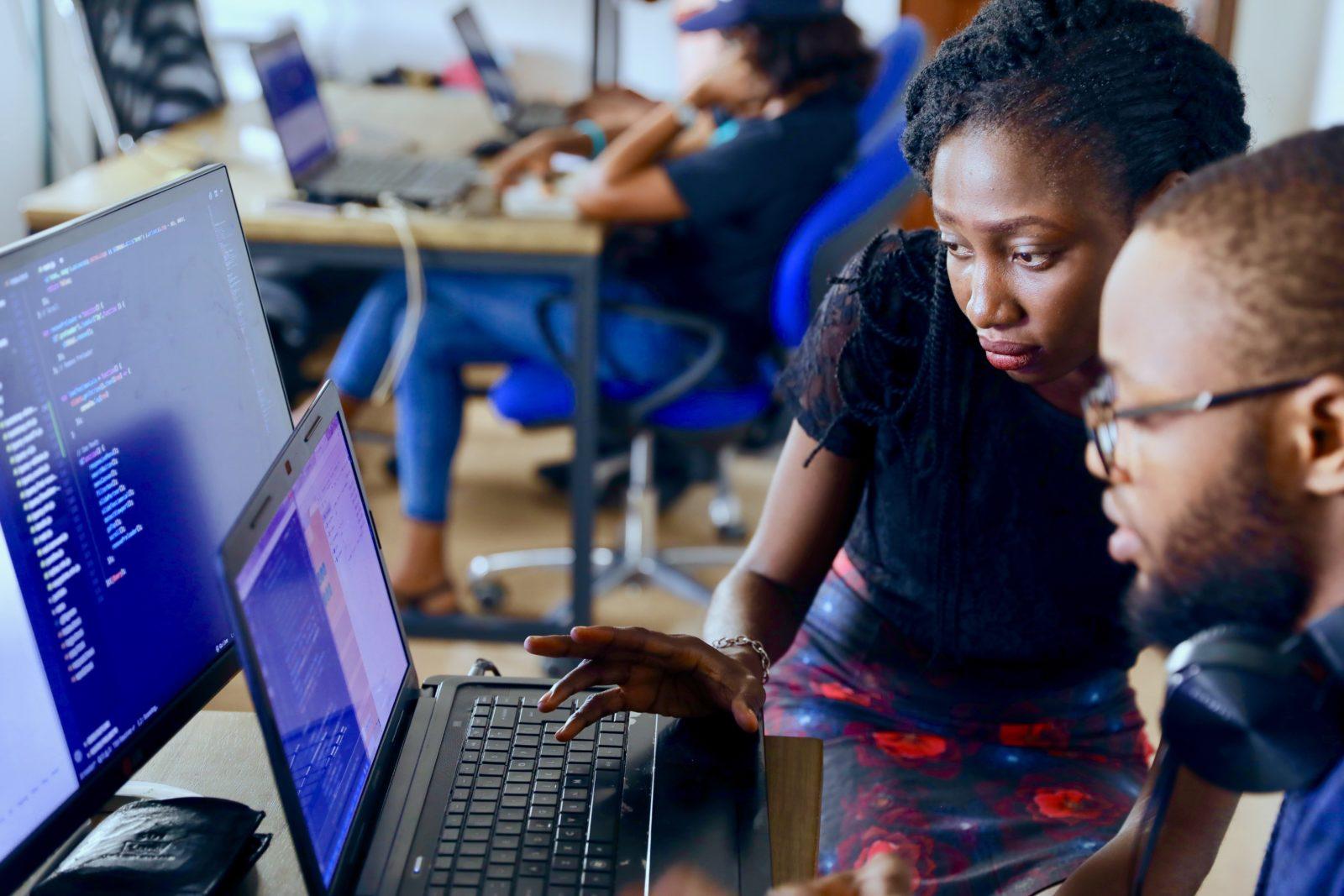 Woman helping Man at Computer